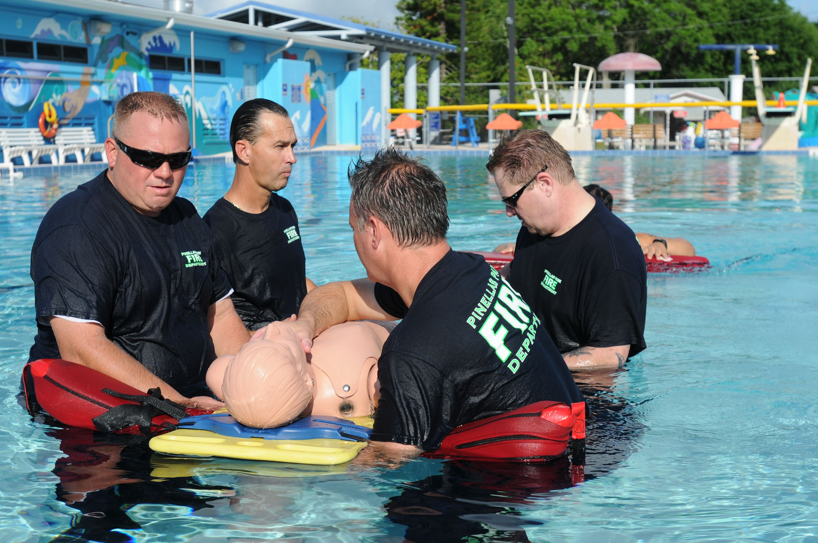 EMS trainees in a pool practicing rescuing people