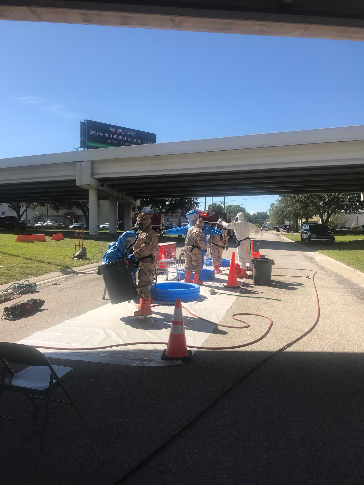 Hazard team workers decontaminate a section of road