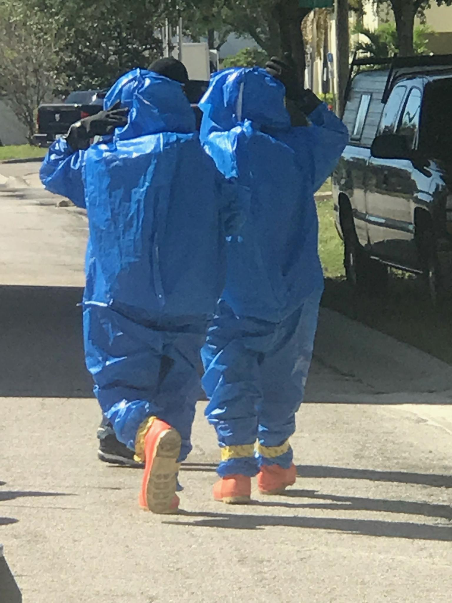 Two workers in haz suits walk down the street