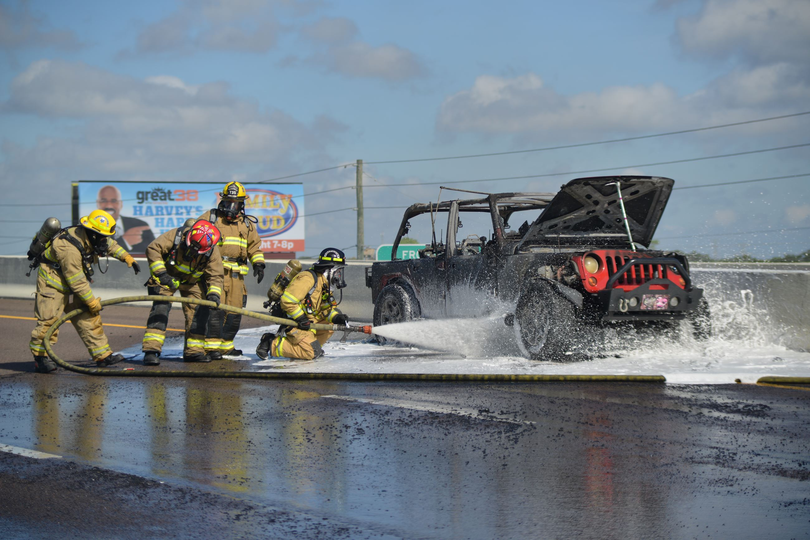 Team members spray down a fire-wrecked vehicle