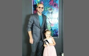 Male dressed in suit smiling with his young daughter in pretty dress at daddy daughter dance