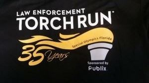 Torch Run logo_ Black shirt with Olympic logo.