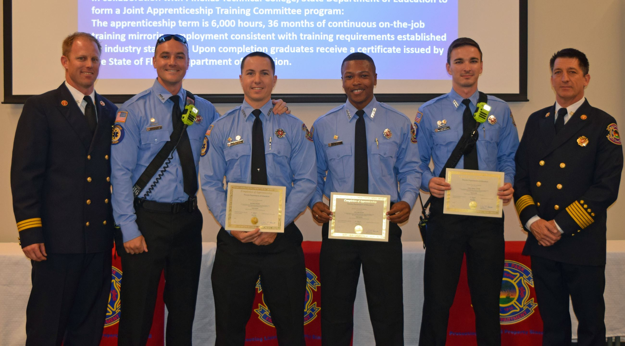 Four firefighters in dress uniform holding certificates of achievement